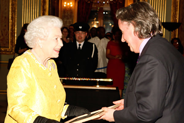 Maestro Paul Carroll presenting a framed score to HM The Queen